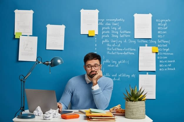 concentrated bearded web developer improves new website version sits white table loaded with notepads snack cup tea potted plant looks sadly problem project leans hand 273609 34544
